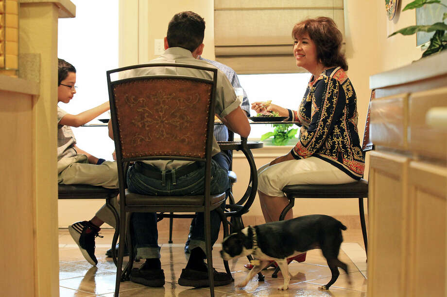 Diane Lerma, 49, (from right) talks with her family Stephen Lerma, 18, Vincent Lerma, 11, and David Lerma, 51, (not pictured) while having lunch as their dog Holly passes Sunday Aug. 25, 2013 at their home. Photo: Edward A. Ornelas / San Antonio Express-News