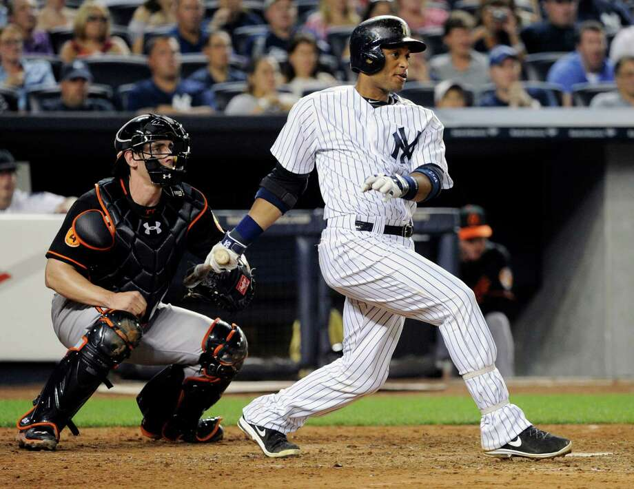 New York Yankees' Robinson Cano follows through on a two-RBI single as Baltimore Orioles catcher Taylor Teagarden, left, looks on during the fifth inning of a baseball game, Friday, Aug. 30, 2013, at Yankee Stadium in New York. (AP Photo/Bill Kostroun) ORG XMIT: NYY113 Photo: Bill Kostroun / FR51951 AP