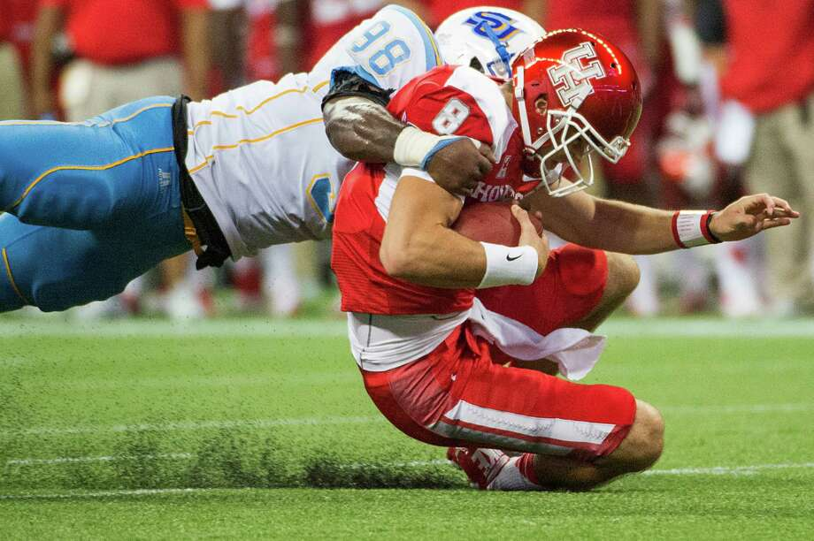 Houston quarterback David Piland is brought down by Southern University linebacker Daniel Brown (98) as he scrambles for a first down. Photo: Smiley N. Pool, Houston Chronicle / © 2013  Houston Chronicle