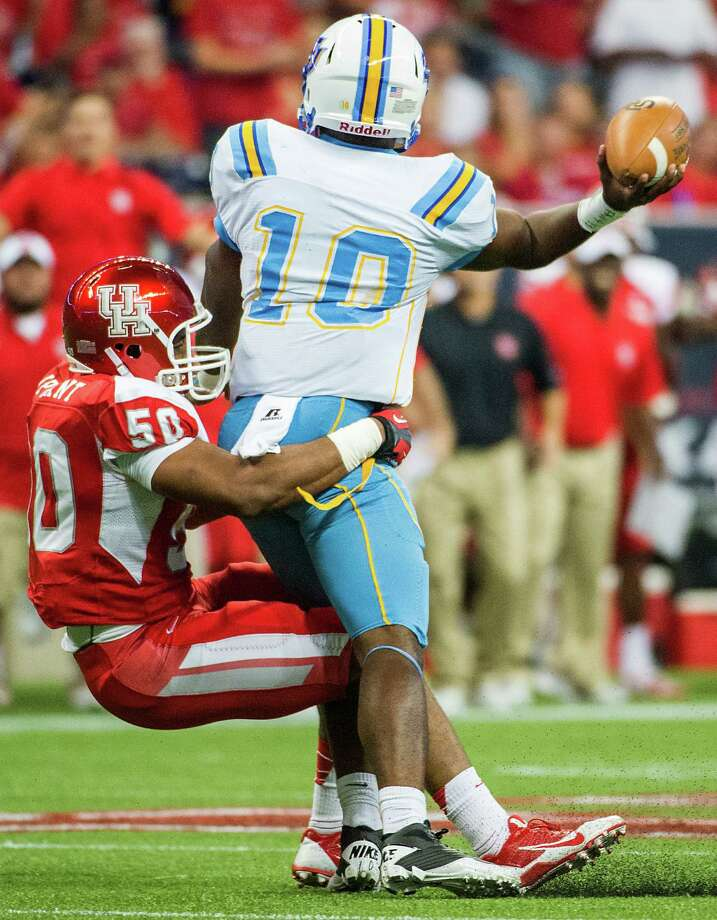 Southern University quarterback Dray Joseph gets off a pass as he is dragged down by Houston linebacker Efrem Oliphant. Photo: Smiley N. Pool, Houston Chronicle / © 2013  Houston Chronicle