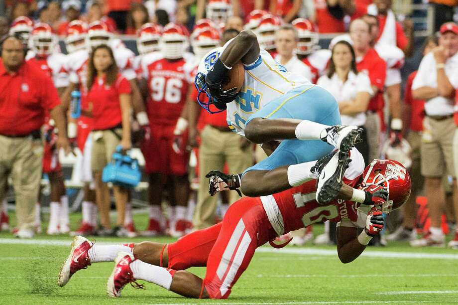 Southern tight end Bradley Coleman (84) is upended by Houston defensive back Zachary McMillian. Photo: Smiley N. Pool, Houston Chronicle / © 2013  Houston Chronicle