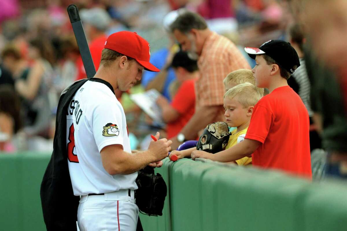 ValleyCats' pitcher Charles Basford, left, signs autographs for young fans before their baseball game against the Vermont Lake Monsters on Friday, Aug. 30, 2013, at Bruno Stadium in Troy, N.Y. (Cindy Schultz / Times Union)