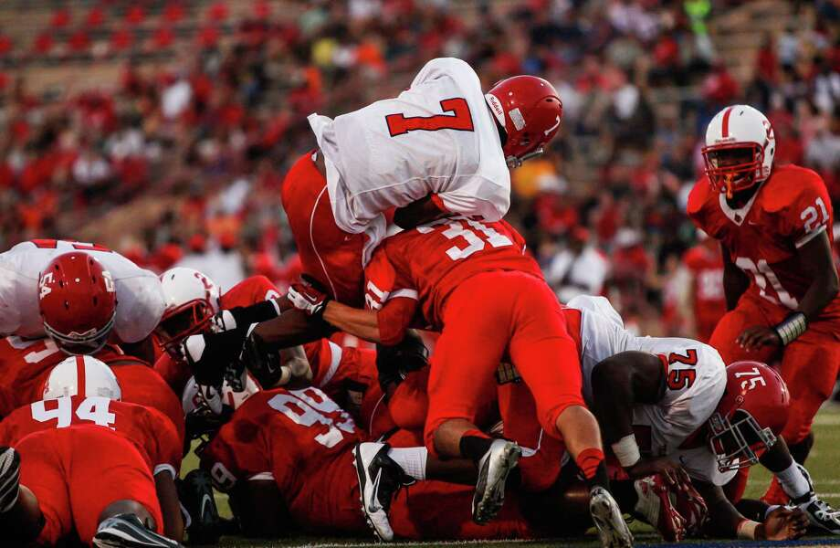 Alief-Taylor quarterback Remi Olonade (7) leaps over the pile for a touchdown during the second quarter of a high school football game at Butler Stadium on Friday, Aug. 30, 2013, in Houston, Texas.  ( Andrew Richardson / For the Chronicle ) Photo: Andrew Richardson, Freelance / © 2013 Andrew Richardson