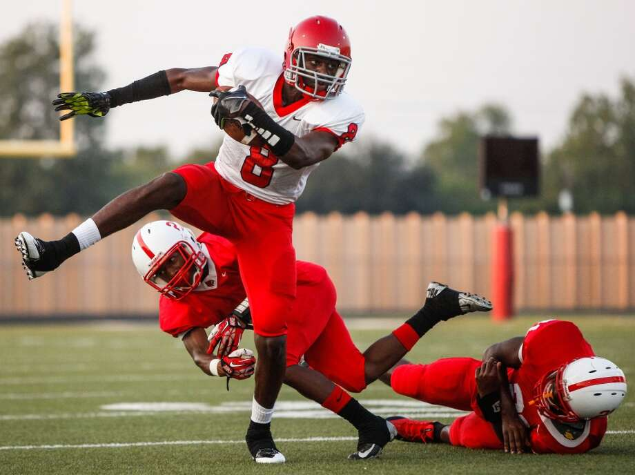 Alief-Taylor wide receiver Keenen Brown (8) breaks a tackle during the first quarter of a high school football game at Butler Stadium on Friday, Aug. 30, 2013, in Houston, Texas.  ( Andrew Richardson / For the Chronicle ) Photo: Andrew Richardson, For The Chronicle