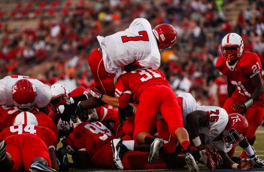 Alief-Taylor quarterback Remi Olonade (7) leaps over the pile for a touchdown during the second quarter of a high school football game at Butler Stadium on Friday, Aug. 30, 2013, in Houston, Texas.  ( Andrew Richardson / For the Chronicle ) Photo: Andrew Richardson, For The Chronicle