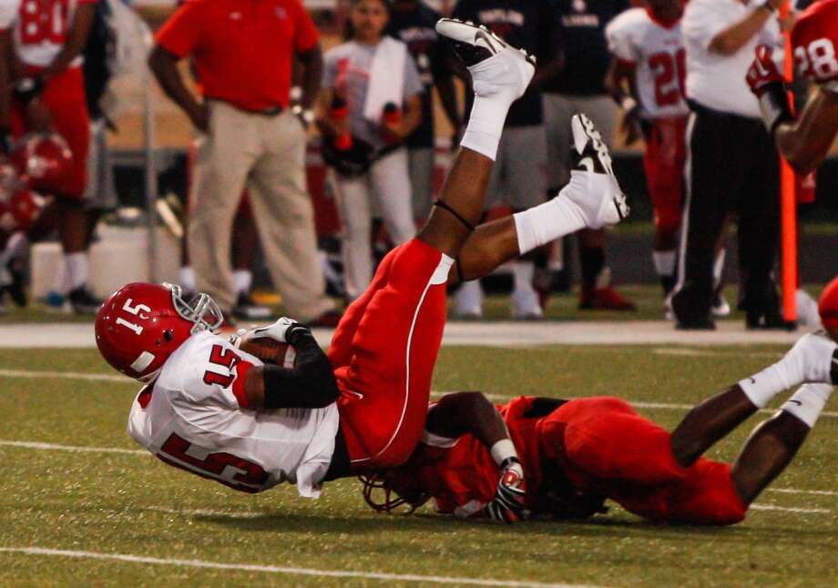 Alief-Taylor wide receiver Romello Brooker (15) has his legs taken out from under him during the second quarter of a high school football game at Butler Stadium on Friday, Aug. 30, 2013, in Houston, Texas.  ( Andrew Richardson / For the Chronicle ) Photo: Andrew Richardson, For The Chronicle