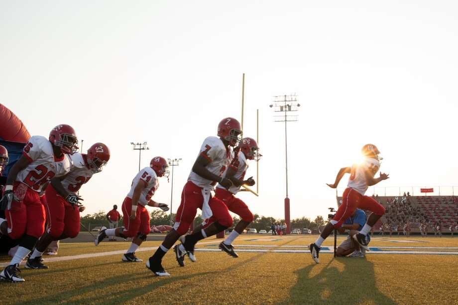 The Alief-Taylor Lions run onto the field prior to the first quarter of a high school football game at Butler Stadium on Friday, Aug. 30, 2013, in Houston, Texas.  ( Andrew Richardson / For the Chronicle ) Photo: Andrew Richardson, For The Chronicle
