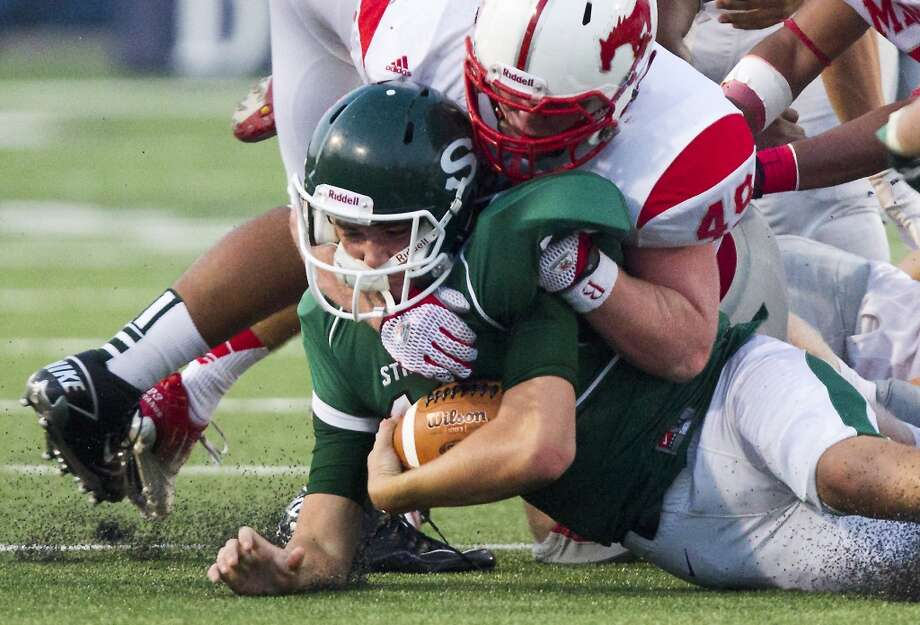 Stratford quarterback Freddy Price is taken down by Memorial linebacker Tug White during the first half of a high school football game at Tully stadium on Friday, Aug. 30, 2013, in Houston. ( J. Patric Schneider / For the Chronicle ) Photo: J. Patric Schneider, For The Chronicle