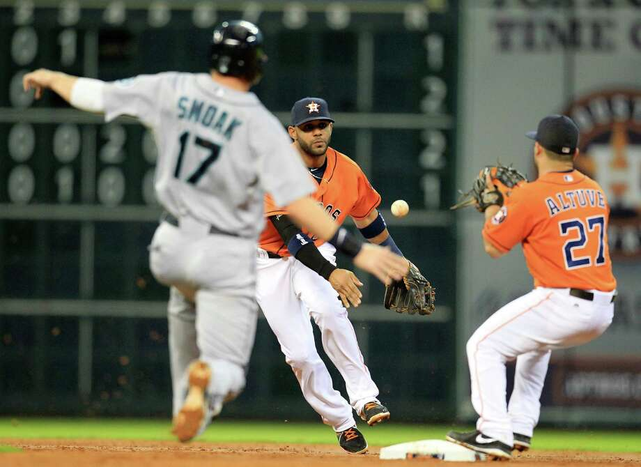 Astros shortstop Jonathan Villar, center, makes the toss to second baseman Jose Altuve, right, to force Seattle's Justin Smoak on Henry Blanco's fielder's-choice grounder in the second inning Friday night. Photo: Karen Warren, Staff / © 2013 Houston Chronicle
