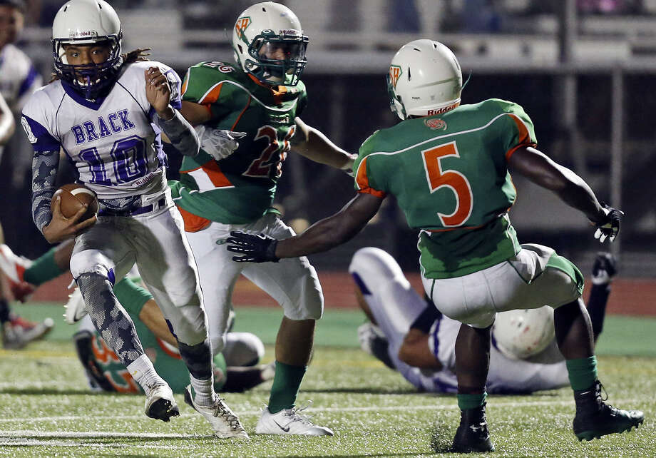 Brackenridge QB Ramon Richards finds running room and eludes Sam Houston's Steven Garcia (center) and Tomaria Stringfellow en route to scoring during the first half at the Wheatley Heights Sports Complex.