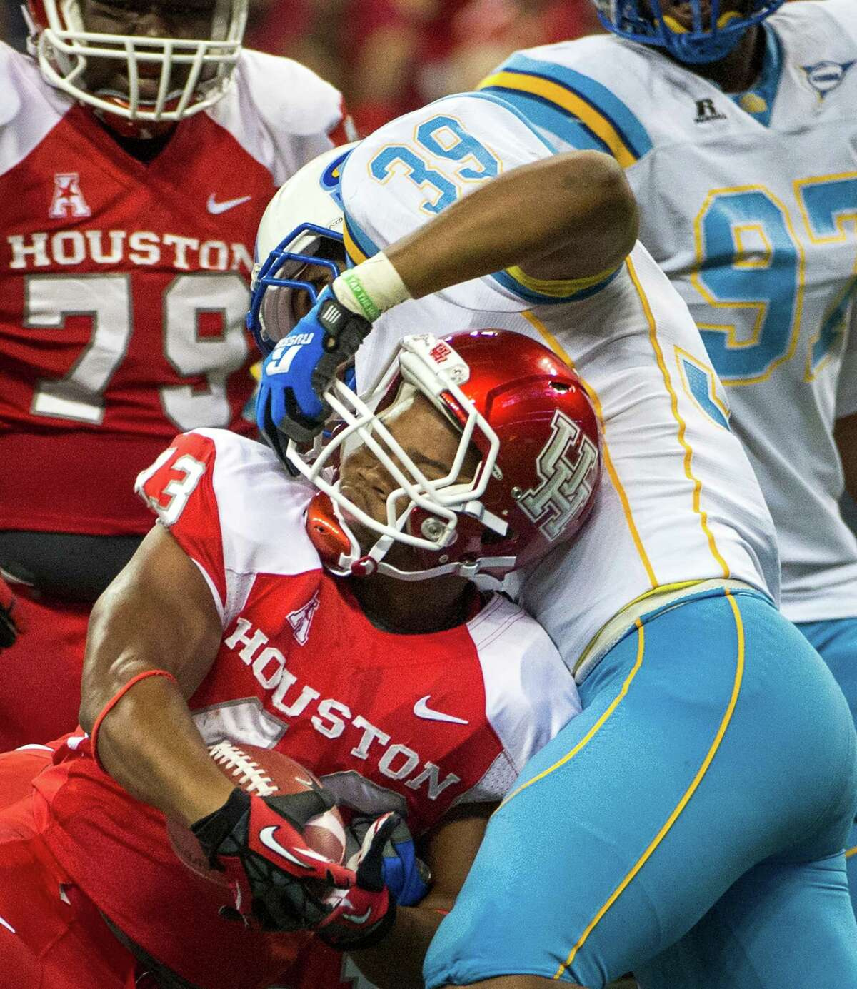 Houston running back Justin Hicks (43) pushes past Southern University linebacker Demetrius Carter (39) to score on a 1-yard touchdown run during the second half of a college football game at Reliant Stadium, Friday, Aug. 30, 2013, in Houston. Houston won the game 62-13.