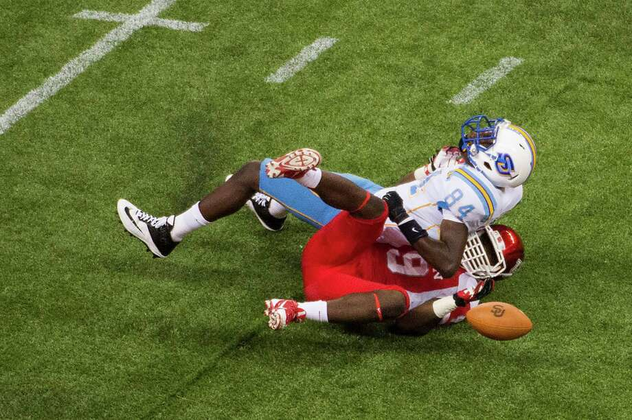Southern University tight end Bradley Coleman (84) loses the ball as he is hit by Houston linebacker Derrick Mathews (49). Photo: Smiley N. Pool, Houston Chronicle / © 2013  Houston Chronicle
