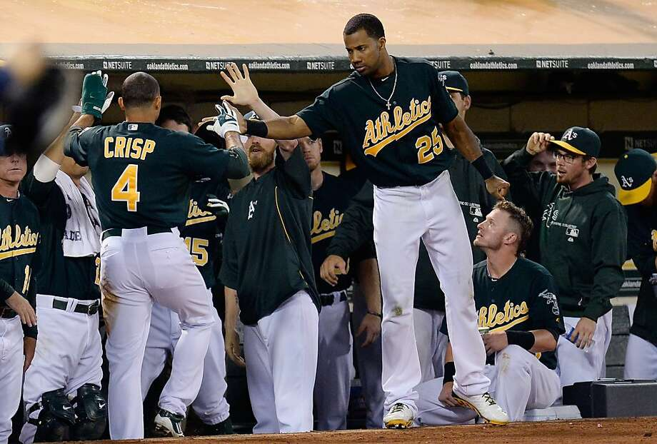 Coco Crisp, left, gets a warm welcome after scoring the go-ahead run in the eighth against Tampa Bay. Photo: Thearon W. Henderson, Getty Images