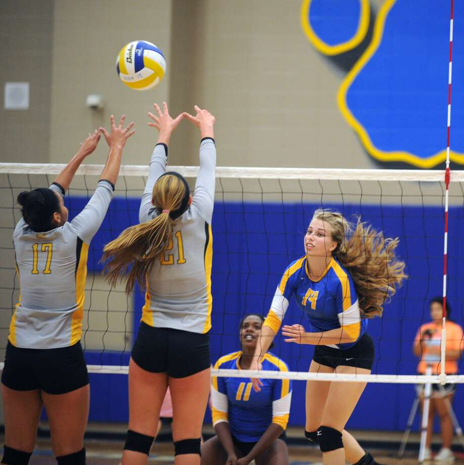 Right, Klein outside hitter  Courtney Taylor (14) hit the ball over the net and scored a point. Photo: Eddy Matchette, For The Chronicle / Freelance