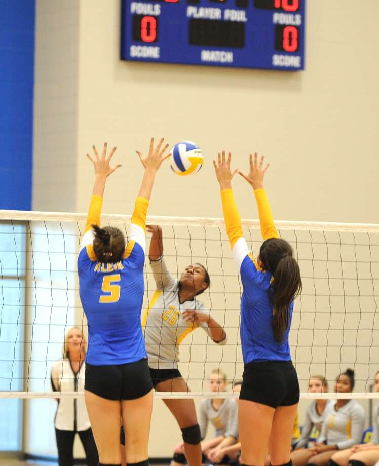 Facing, Tori Fluellen (26) hits the ball between two Klein defenders at the net. Photo: Eddy Matchette, For The Chronicle / Freelance