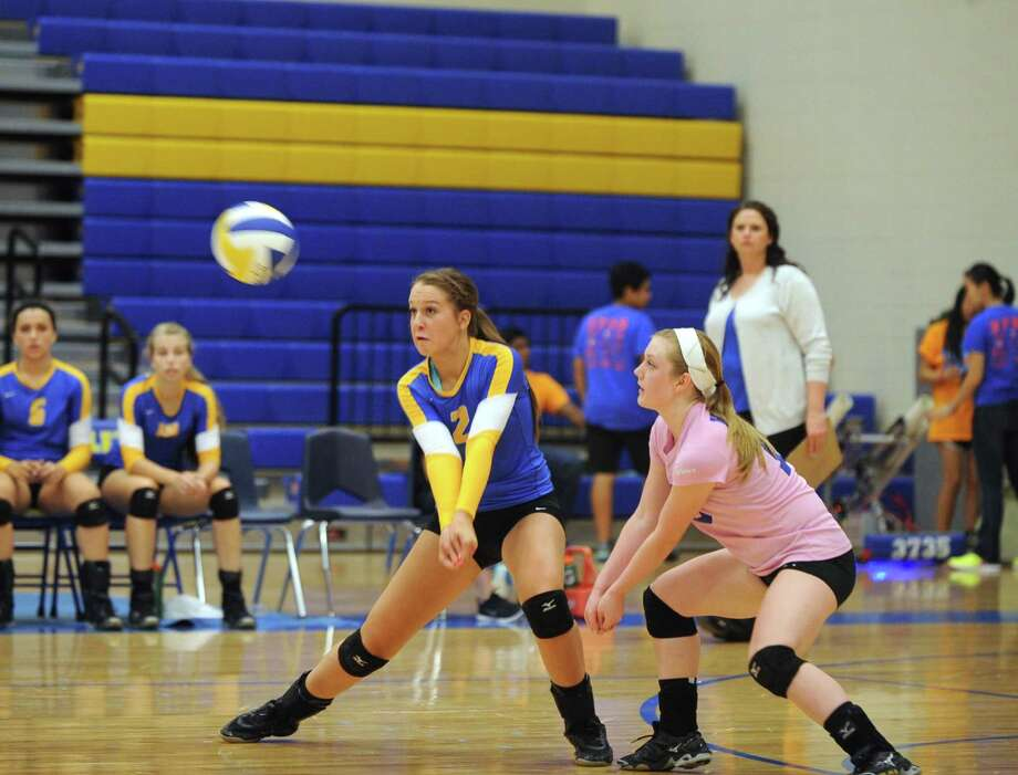 Left, Meagan Bauer (2) and Erin Brown (15) ready themselves to catch up a ball hit by Klein Oak. Photo: Eddy Matchette, For The Chronicle / Freelance