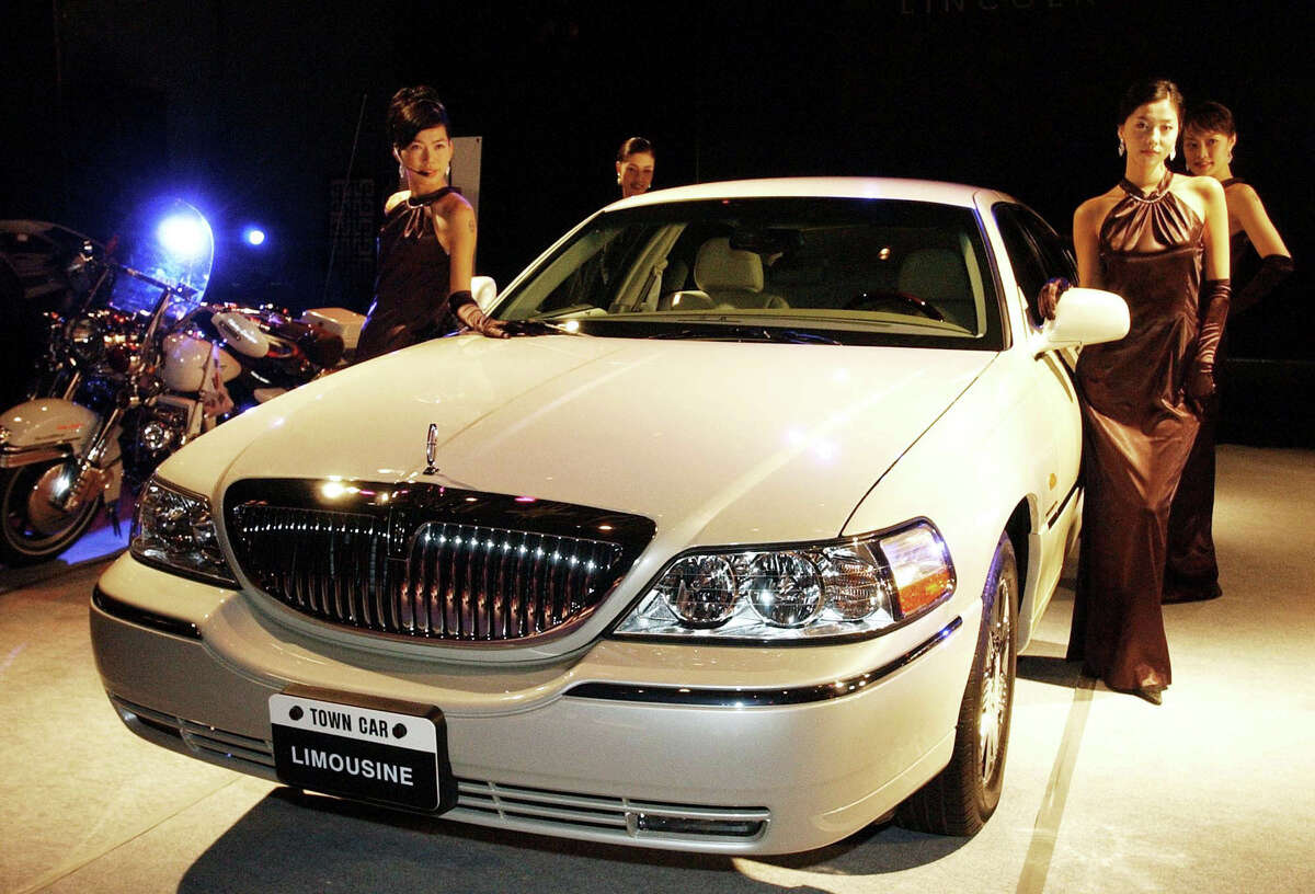 Models pose with Ford Motor Company's Lincoln Town Car Limousine during a media unveiling in Seoul Tuesday, Oct. 29, 2002. The Lincoln Town Car, priced at 82 million Korean won ($65,600), is equipped with V8 SOHC (4,600cc) engine. (AP Photo/Ahn Young-joon)