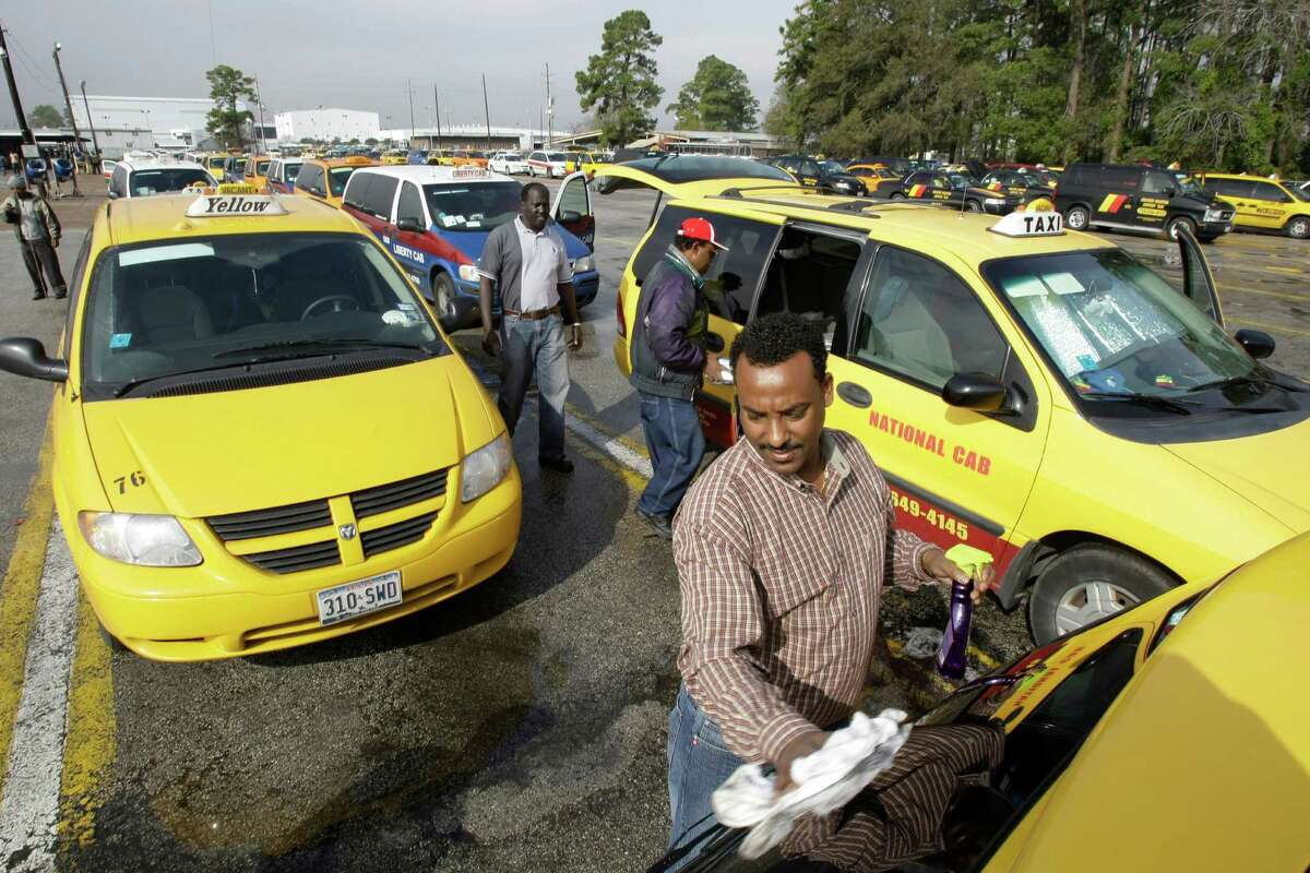 Sahlu Aberra cleans the back window of his cab at the Houston airport taxi staging area near George Bush Intercontinental Airport Tuesday, Jan. 22, 2008, in Houston. ( Brett Coomer / Chronicle )