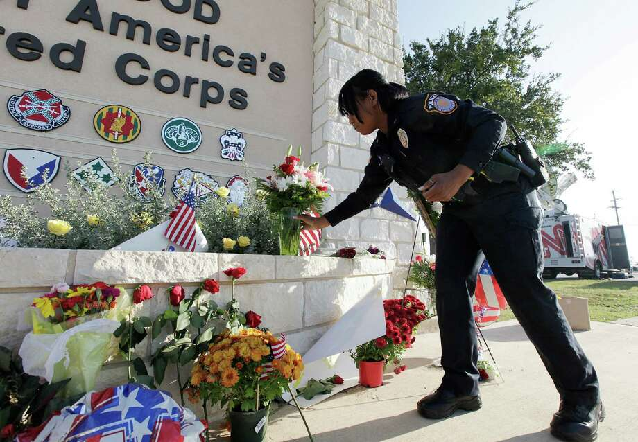 In this Nov. 10, 2009 photo, a Fort Hood police officer places flowers at the base's Bernie Beck Main Gate. the lives lost to the Marvin Leath Visitors Center at the Bernie Beck Main Gate at Fort Hood, Texas. Maj. Nidal Hasan is charged in the 2009 shooting rampage at Fort Hood that left 13 dead and more than 30 others wounded. Hasan doesn't deny that he carried out the rampage, but military law prohibits him from entering a guilty plea because authorities are seeking the death penalty. If he is convicted and sentenced to death in a trial that starts Tuesday, Aug. 6, 2013, there are likely years, if not decades, of appeals ahead. (AP Photo/Temple Daily Telegram, Scott Gaulin, File) Photo: Scott Gaulin, MBR / Temple Daily Telegram