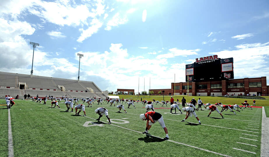 Cardinals take the field to stretch after a break due to lightning during the Lamar University footb