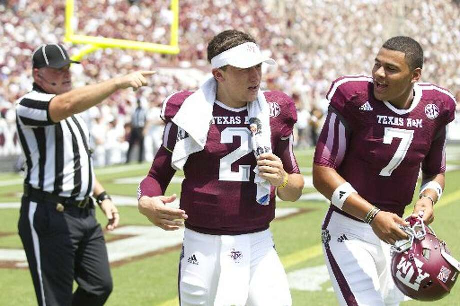Texas A&M quarterback Johnny Manziel is told to get off the field by an official after an Aggie touchdown against Rice during the second quarter. Photo: Brett Coomer, Houston Chronicle