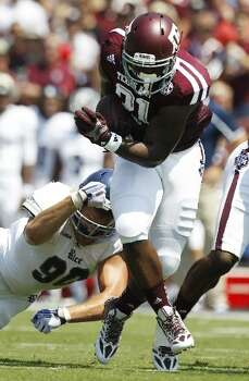 Texas A&M running back Tra Carson breaks away from Rice defensive end Cody Bauer during the first quarter. Photo: Brett Coomer, Houston Chronicle