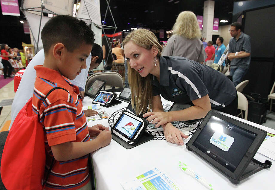 BiblioTech head librarian Ashley Eklof (right) demonstrates to Adonai Rodriguez, 9, how to use one of the interactive readers from the new, book-less library from Bexar County at Festival People en Español at the Henry B. Gonzalez Convention Center on Saturday, Aug. 31, 2013. The event is a celebration of Latino culture, music and community. Photo: Kin Man Hui, San Antonio Express-News / ©2013 San Antonio Express-News