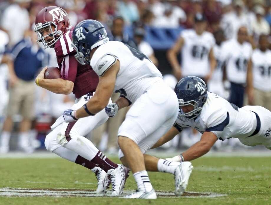 Texas A&M quarterback Johnny Manziel (2) is chased by Rice linebackers Nick Elder (46) Michael Kutzler (42) during the third quarter of an NCAA college football game at Kyle Field Saturday, Aug. 31, 2013, in College Station. ( Brett Coomer / Houston Chronicle ) Photo: Brett Coomer, Houston Chronicle