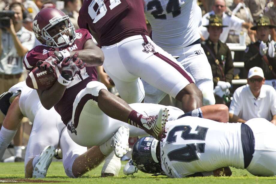 Texas A&M running back Tra Carson (21) scores on a 2-yard touchdown run over Rice linebacker Michael Kutzler (42) during the second quarter of an NCAA college football game at Kyle Field Saturday, Aug. 31, 2013, in College Station. ( Brett Coomer / Houston Chronicle ) Photo: Brett Coomer, Houston Chronicle