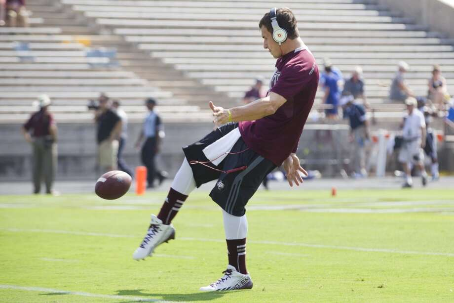 Texas A&M quarterback Johnny Manziel kicks a football while warming up before the Aggies' NCAA college football game against Rice at Kyle Field Saturday, Aug. 31, 2013, in College Station. ( Brett Coomer / Houston Chronicle ) Photo: Brett Coomer, Houston Chronicle