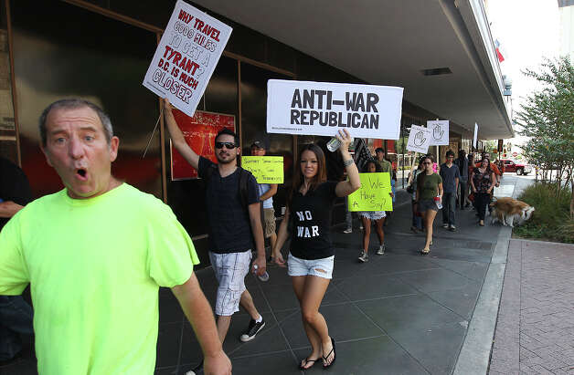 "Anti-war protestors make their way along Alamo Street near Rivercenter Mall on Saturday, Aug. 31. 2013. About a dozen people carried signs and chanted sayings such as ""no war"" as they walked along downtown. Photo: Kin Man Hui, San Antonio Express-News / ©2013 San Antonio Express-News"