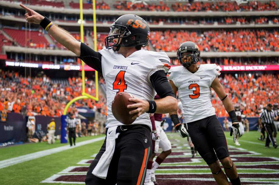 Oklahoma State quarterback J.W. Walsh (4) celebrates with wide receiver Marcell Ateman (3) after scoring on a 1-yard touchdown run during the first half of the AdvoCare Texas Kickoff college football game against Mississippi State at Reliant Stadium, Saturday, Aug. 31, 2013, in Houston. Photo: Smiley N. Pool, Houston Chronicle / © 2013  Houston Chronicle
