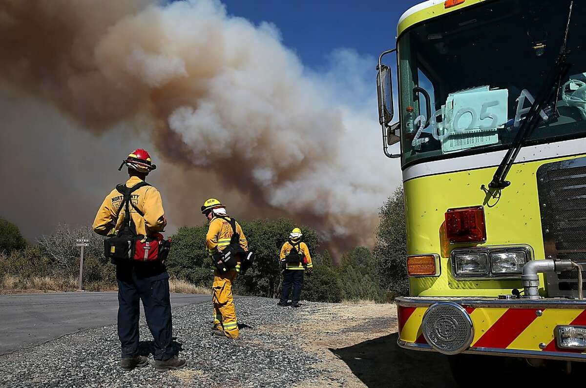 GROVELAND, CA - AUGUST 22: Firefighters monitor a plume of smoke from the Rim Fire on August 22, 2013 in Groveland, California. The Rim Fire continues to burn out of control and threatens 2,500 homes outside of Yosemite National Park. Over 1,000 firefighters are battling the blaze that was reduced to only 2 percent containment after it nearly tripled in size overnight. (Photo by Justin Sullivan/Getty Images)
