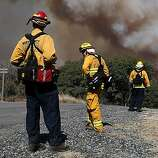 Firefighters monitor a plume of smoke from the Rim Fire on August 22, 2013 in Groveland, California. The Rim Fire continues to burn out of control and threatens 2,500 homes outside of Yosemite National Park. Over 1,000 firefighters are battling the blaze that was reduced to only 2 percent containment after it nearly tripled in size overnight.