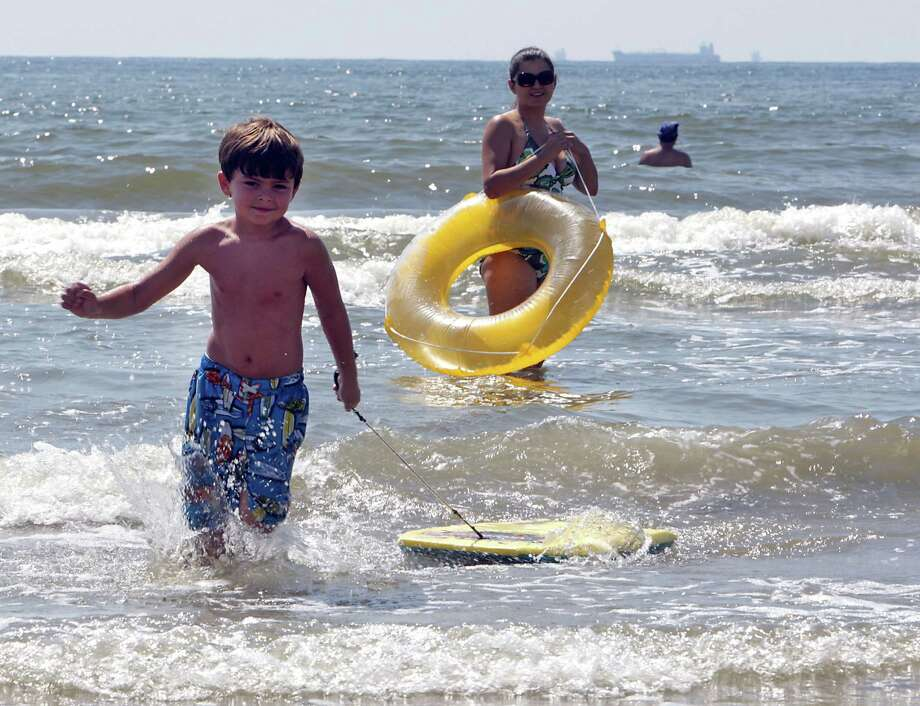 Six-year-old Carter Burnett, left, runs with a body board as his mother Jessica Alexander, right, looks on near Beach Town Saturday, Aug. 31, 2013, in Galveston. Photo: James Nielsen, Houston Chronicle / © 2013  Houston Chronicle