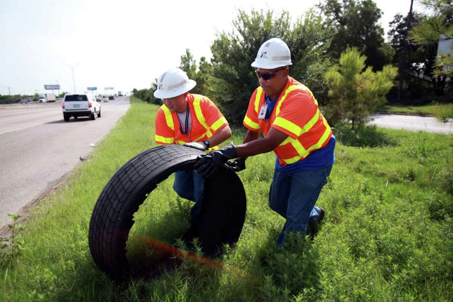 Jose Medrano and Kenneth Walker of Texas Department of Transportation remove debris from the highway along Loop 610 on Tuesday, Aug. 27, 2013, in Houston. Photo: Mayra Beltran, Houston Chronicle / © 2013 Houston Chronicle