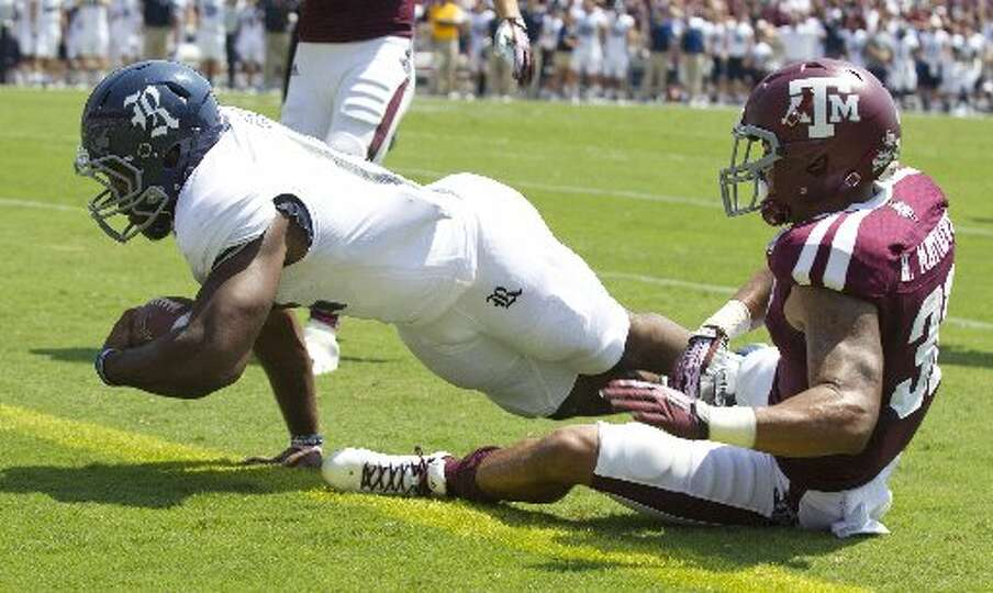 Rice running back Charles Ross dives into the end zone past Texas A&M linebacker Tyrell Taylor for a