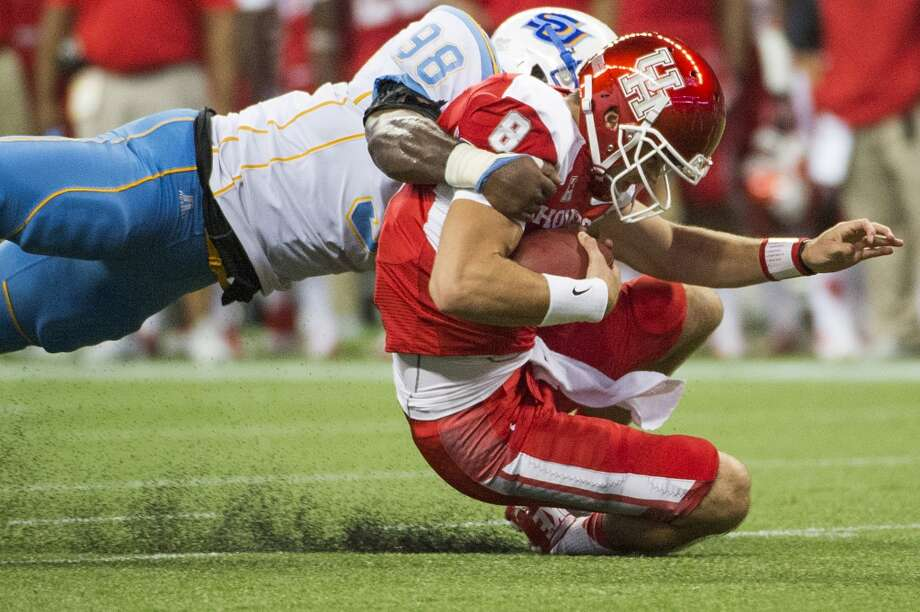 Houston quarterback David Piland is brought down by Southern University linebacker Daniel Brown. Photo: Smiley N. Pool, Houston Chronicle