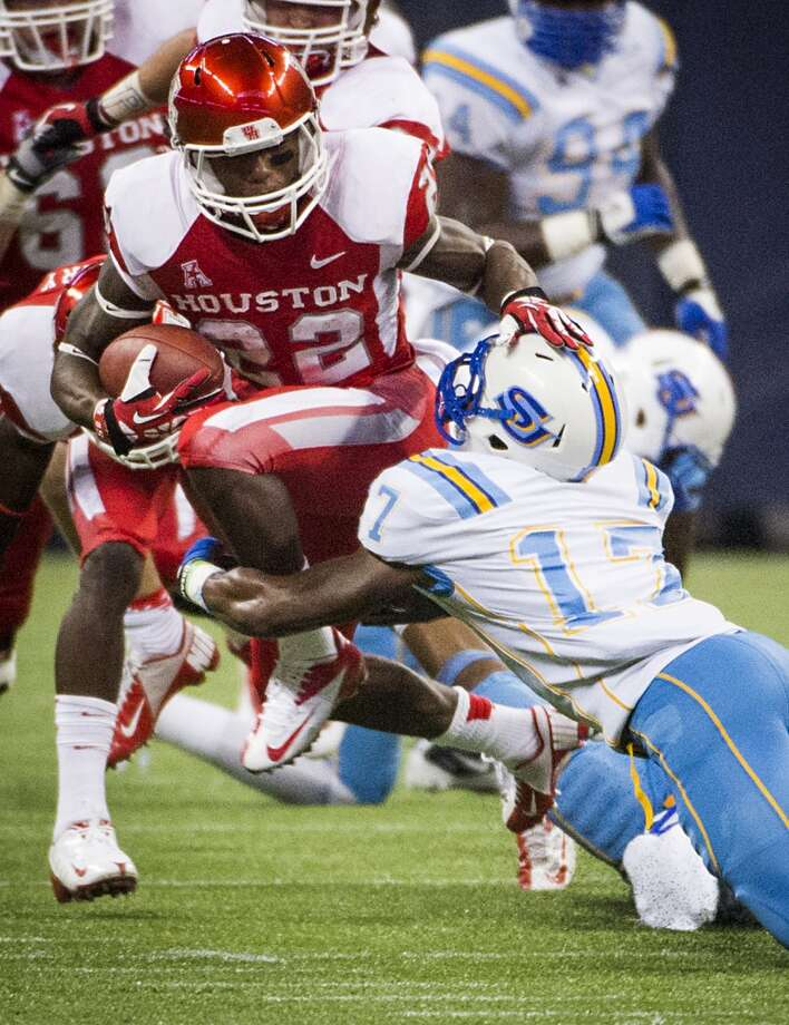 Houston running back Ryan Jackson gets past Southern University defensive back Omar Cook during the first half. Photo: Smiley N. Pool, Houston Chronicle