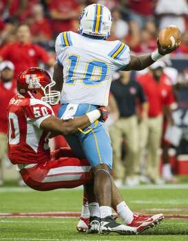 Southern University quarterback Dray Joseph (10) gets of a pass as he is dragged down by Houston linebacker Efrem Oliphant (50) during the first half. Photo: Smiley N. Pool, Houston Chronicle