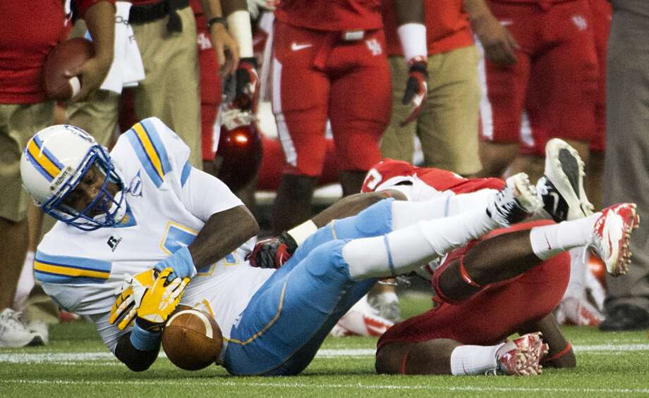 Southern University wide receiver Samuel Altman fumbles as he is hit by Houston defensive back Thomas Bates. Photo: Smiley N. Pool, Houston Chronicle
