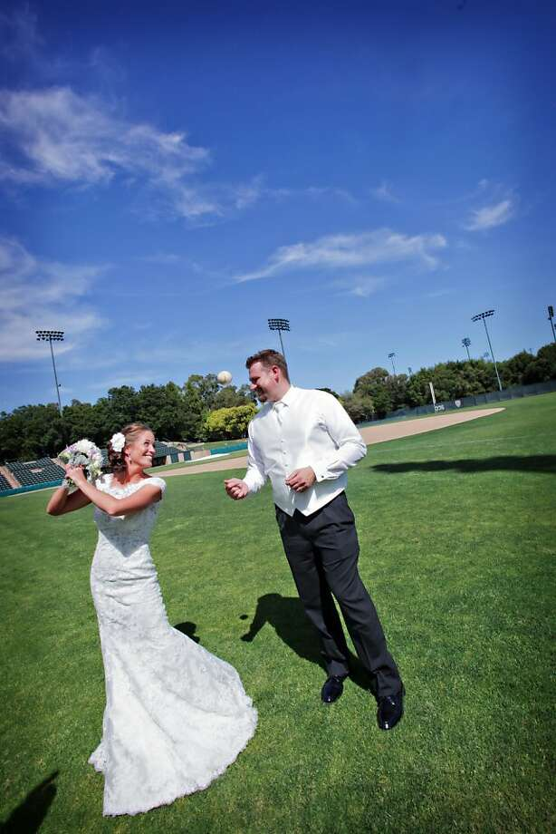 S.F. Giants fan Katie McGlennon pretends to swing her bouquet like a bat as Drew Ehrlich, a former pitcher for the Stanford baseball team and current co-owner of San Jose's Strike Brewing Co., lobs a pitch to her. Photo: Daniel Lunghi Photography