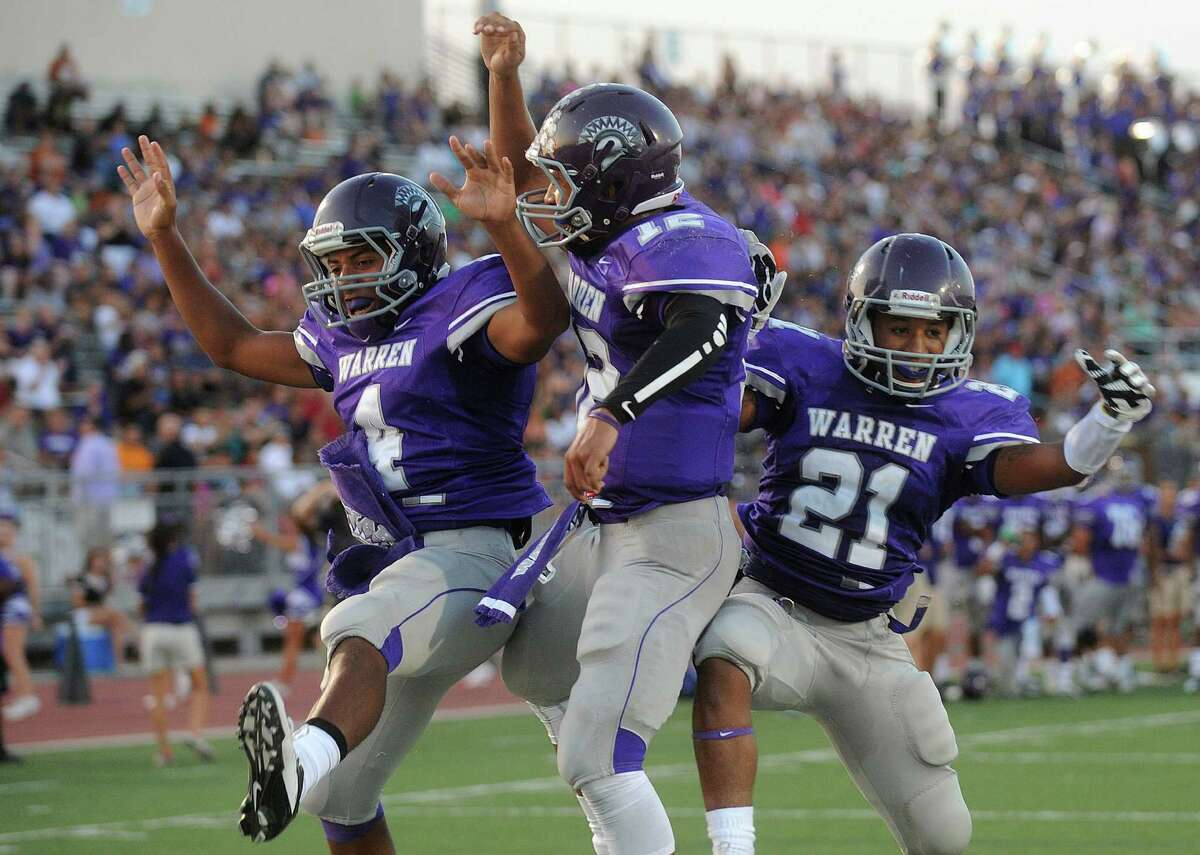 Warren quarterback Jordan Sneed, middle, celebrates with teammates Aedric Robinson, left, and Mark January after Sneed scored a first-half touchdown against MacArthur at Gustafson Stadium on Saturday, Aug. 31, 2013.