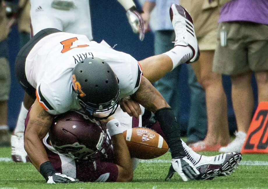 Oklahoma State safety Shamiel Gary dislodges the ball from Mississippi State quarterback Tyler Russell, who struggled to get untracked against the Cowboys' defense. Photo: Smiley N. Pool, Staff / © 2013  Houston Chronicle