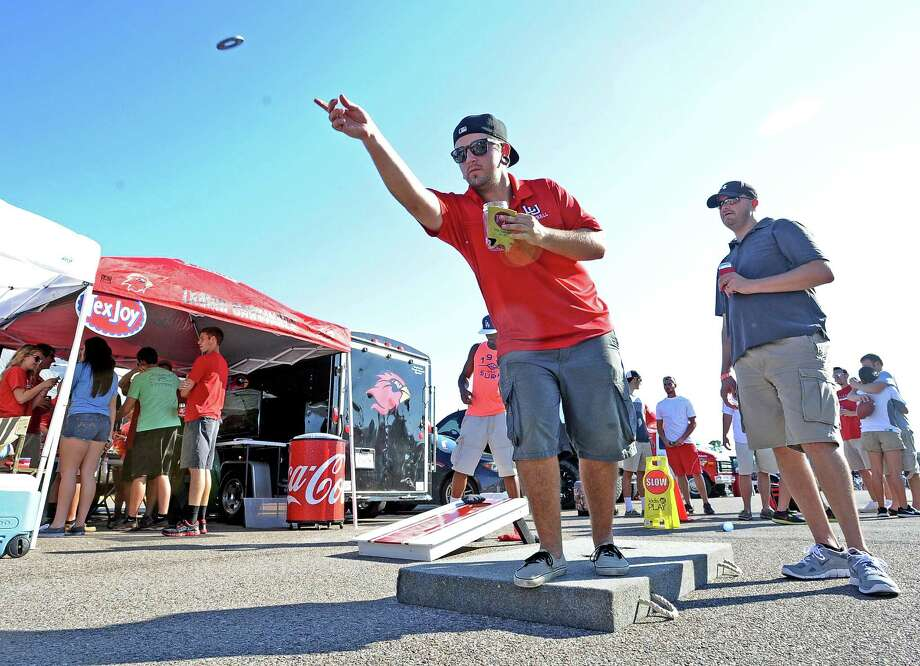 Derek Ray throws washers at his tent on Saturday, August 31, 2013, at the Lamar University tailgating party.   Photo taken: Randy Edwards/The Enterprise Photo: Randy Edwards, Photojournalist / Enterprise