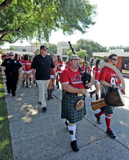 Coach Ray Woodard leads the football team to Provost-Umphrey Stadium on Saturday, August 31, 2013, a