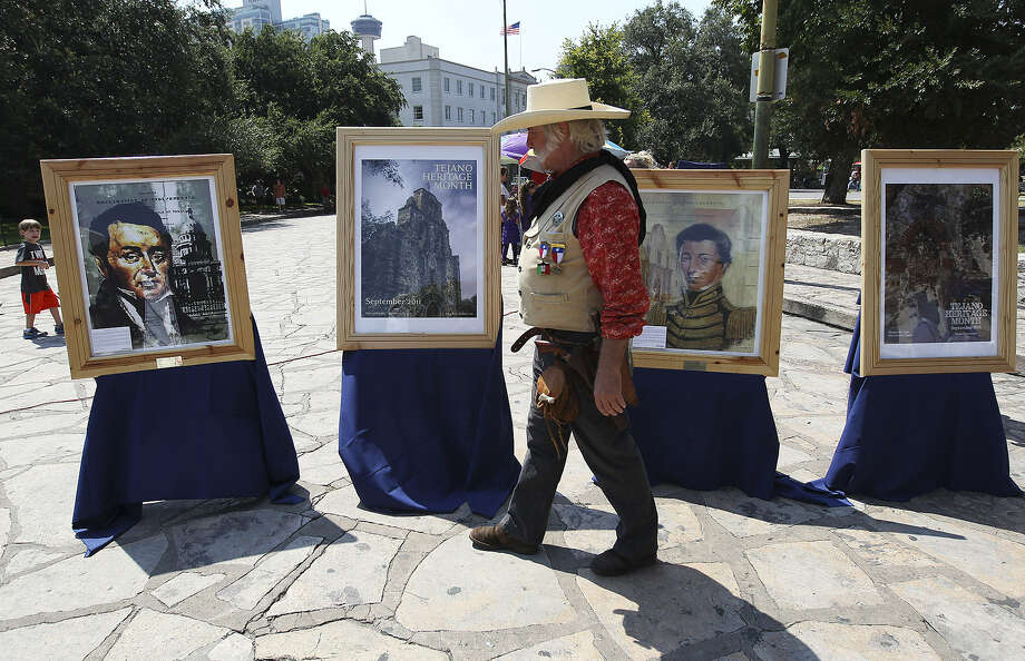 Re-enactor Bill Grisham, dressed as a Texan from the 1850s, looks at posters from previous Tejano Heritage Month celebrations at Alamo Plaza. The event included food, music, entertainment and history. Photo: Photos By Kin Man Hui / San Antonio Express-News