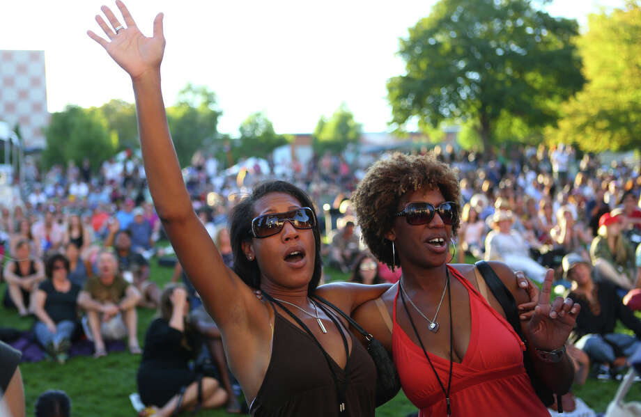 Janea Davis an Teresa Davis sing along with the Total Experience Gospel Choir at the Mural Amphitheater during the first day of Bumbershoot on Saturday, August 31, 2013. Photo: JOSHUA TRUJILLO, SEATTLEPI.COM / SEATTLEPI.COM