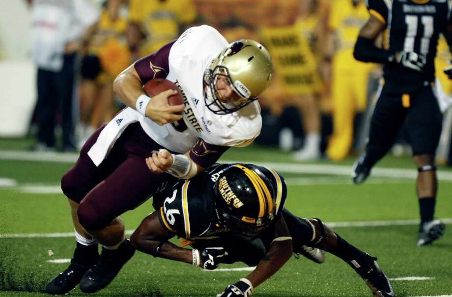 Texas State quarterback Tyler Arndt, top, forces his way past the defense of Southern Mississippi defensive back DeBarriaus Miller (26) into the end zone for a fourth-quarter 17-yard run during their NCAA college football game at Carlsle-Faulkner Field at Roberts Stadium in Hattiesburg Miss., Saturday, Aug. 31, 2013. Texas State won 22-15. (AP Photo/Rogelio V. Solis) Photo: Rogelio V. Solis, Associated Press / AP