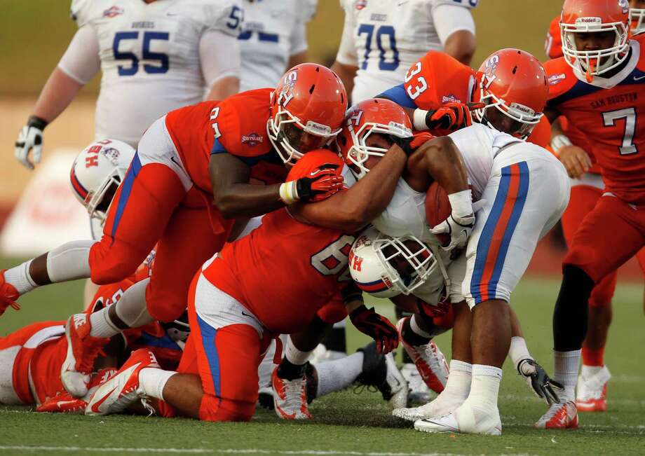 Typical of Houston Baptist's difficult debut, the Huskies' B.J. Kelly goes nowhere  against a wall of Sam Houston State defenders. Photo: Eric Christian Smith, Freelance